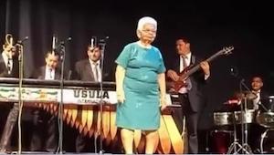 Una señora mayor del vestido azul entra en el escenario. ¡Lo que hace ya en el s
